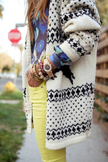 a street style shot of an arm party and fall sweater.