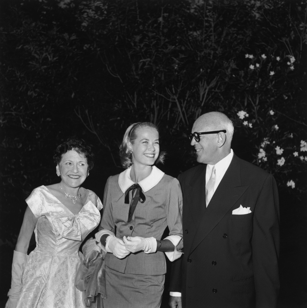 22nd August 1954: American gossip columnist Louella Parsons (1893 - 1972), American actor Grace Kelly (1929 - 1982) and American composer, screenwriter and playwright Jimmy McHugh (1894 - 1969) smiling together outdoors at a party hosted by Parsons and McHugh, Los Angeles, California. Kelly is wearing a skirt suit with a pilgrim collar with white gloves. (Photo by Hulton Archive/Getty Images)